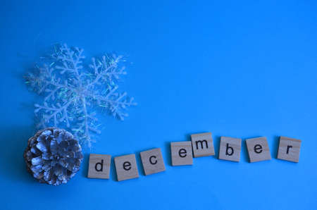 December month written in wooden letters on a blue background. The calendar. Winter. Pine cone, snowflake on the background.
