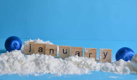 Snow Christmas toys on a blue background. The month of January is written in wooden letters. The calendar.