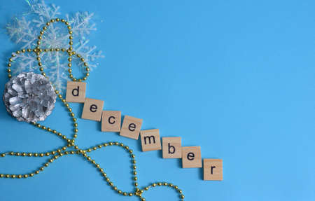 December month written in wooden letters on a blue background. The calendar. Winter. Pine cone, snowflake and beads on the background. Zdjęcie Seryjne