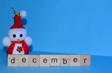 December month written in wooden letters on a blue background. The calendar. Winter. Snowman on the background.
