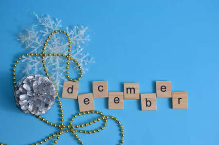 December month written in wooden letters on a blue background. The calendar. Winter. Zdjęcie Seryjne