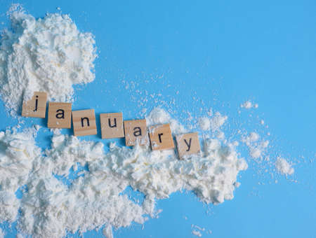 Snow on a blue background. The month of January is written in wooden letters. The calendar. Zdjęcie Seryjne