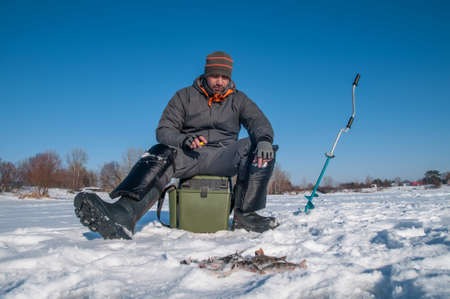 Ice fishing. Fisherman in action