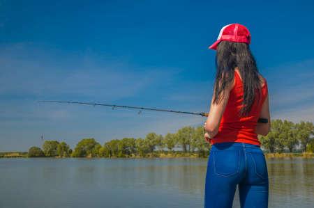 Sexy woman fishing at lake. Back view