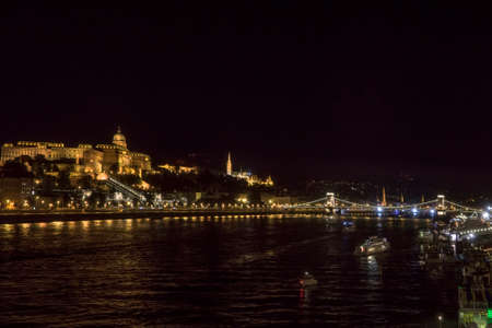 Night Budapest at the river Danube. Buda Castle (Royal Palace) and Chain bridge (Szechenyi lanchid) on background