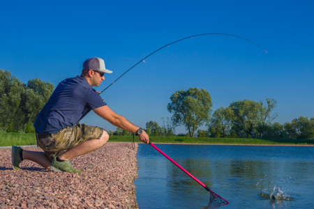 Area trout fishing. Fisherman with spinning rod in action playing fish. Stock Photo