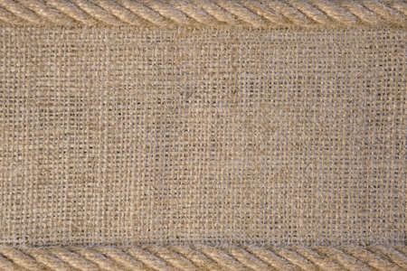 Texture of burlap with cord. Template frame of coarse cloth background Фото со стока