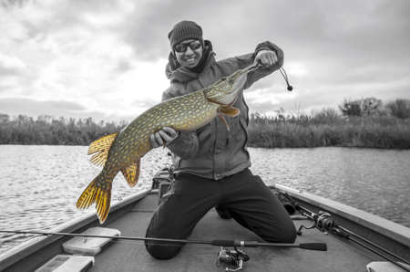 Happy fisherman with big pike fish trophy at the boat with fishing tackles Banque d'images