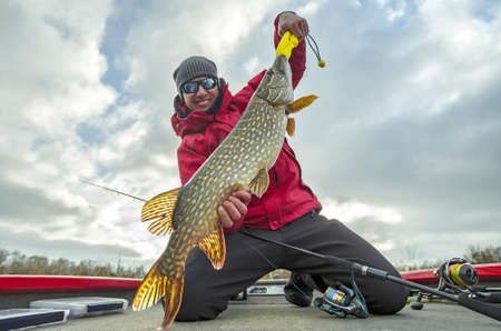 Happy fisherman with big pike fish trophy at the boat with fishing tackles Stock fotó