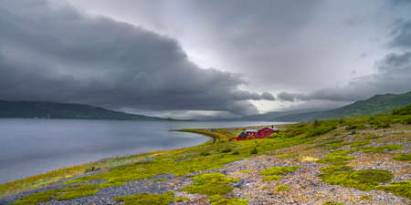 Lonely red house at lake shore in the mountains of Norway