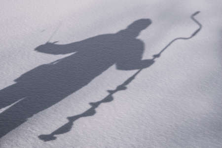 Winter fishing concept. Silhouette of fisherman with ice screw and tackle in hand on snowy ice at lake Standard-Bild