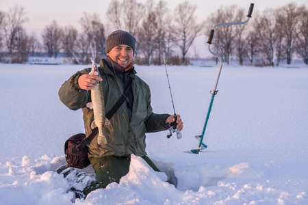 Winter fishing concept. Fisherman in action with trophy in hand. Catching pike fish from snowy ice at lake. 版權商用圖片