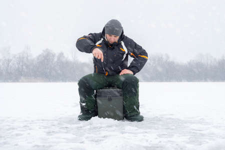 Winter fishing concept. Fisherman in action, catching fish from ice in snowy weather.