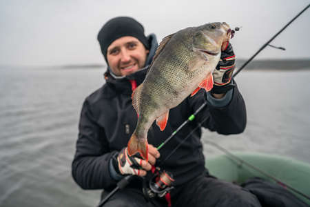 Happy fisherman with big perch fish trophy at boat