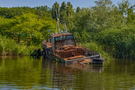 Abandoned old rusty fishing boat on shore