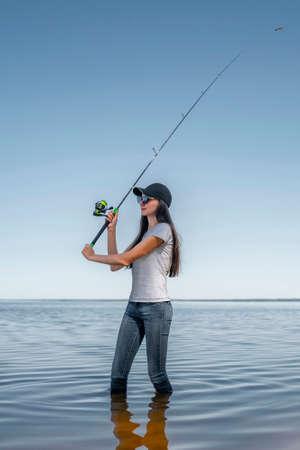 Fishing concept. Young fisherwoman with tackles at lake coast