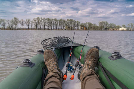 Kayak fishing at lake. Legs of fisherman on inflatable boat with fishing tackle.