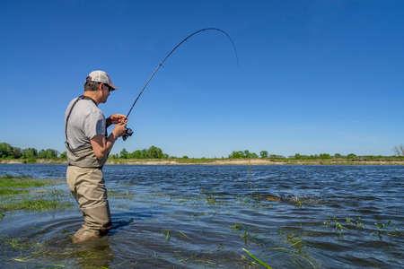 Big pike fishing. Fisherman catch fish in water at river