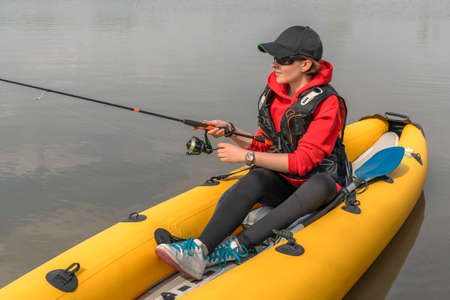 Kayak fishing at lake. Fisherwoman on inflateble boat with fishing tackle. Banque d'images