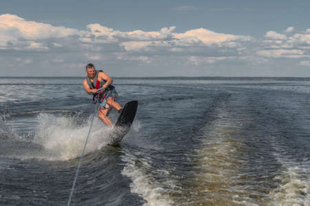 Tense man wakeboarding in a lake and pulled by a boat