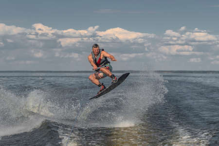 Tense man wakeboarding in a lake and pulled by a boat. Jumping from wave