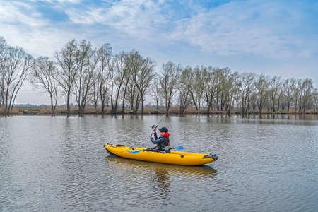 Kayak fishing at lake. Fisherwoman on inflatable boat with fishing tackle.