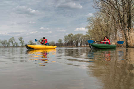 Kayak fishing at lake. Two fisherwomen on inflatable boats with fishing tackle. Stock Photo