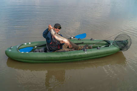 Kayak fishing. Fisherman caught pike fish on inflatable boat with fishing tackle at lake.