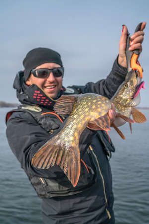 Pike fishing. Happy fisherman with big fish trophy at the boat with tackles Stock fotó
