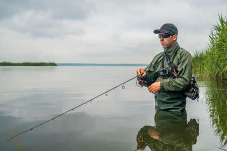 Fishing. Fisherman in action, man catch fish by spinning rod