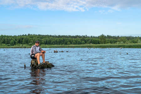 Fishing. Fisherman in action, lonely man catch fish by spinning rod Stock Photo