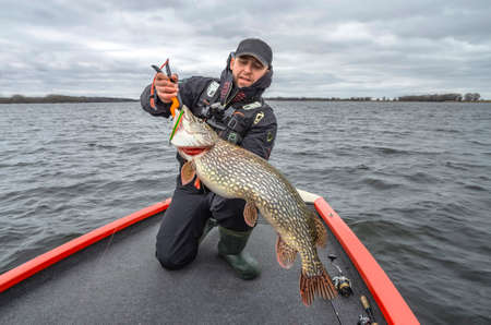 Pike fishing. Happy fisherman with big fish trophy at the boat with tackles Stock Photo