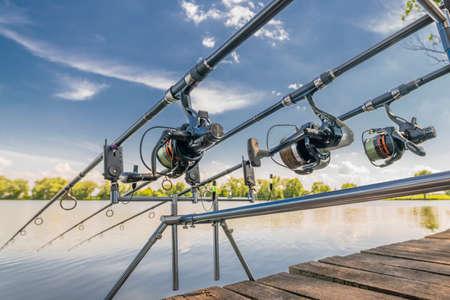Carp fishing. Rods on rod pod on wood platform at lake Stock Photo