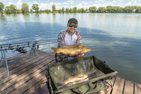 Carp fishing. Fisherman with fish trophy in hands at lake Stock Photo