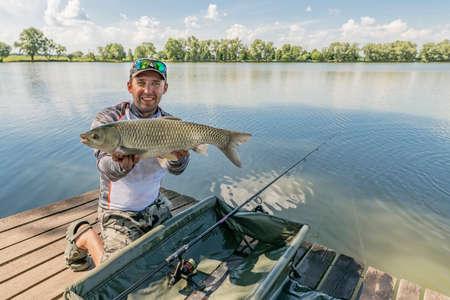 Amur fishing. Fisherman with grass carp fish in hands at lake Stock Photo