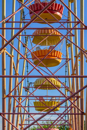Aged and worn vintage ferris wheel. View through metal construction