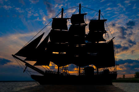Old ancient pirate ship silhouette on peaceful ocean at sunset background Stock Photo