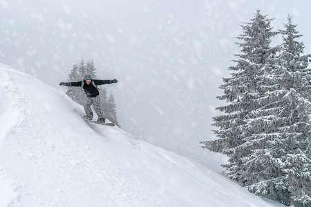 Lo snowboarder guida dalla collina di neve polverosa. Snowboard freeride in montagna. Carpazi invernali