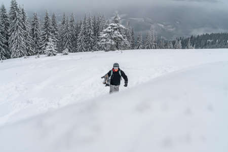 Snowboarder goes up to snow hill. Mountain freeride snowboarding. Winter Carpathians