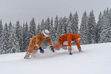 Happy couple people in tiger costumes have fun and enjoy the fresh snow in winter mountains Carpathians.