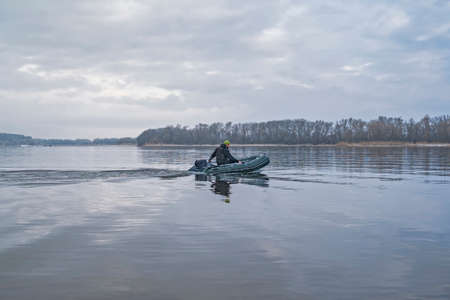 Fishing. Fisherman on inflatable boat with fishing tackle at lake in winter. Stock Photo