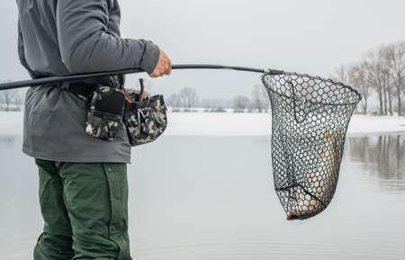 Winter fishing. Fisherman with pike fish in landing net.