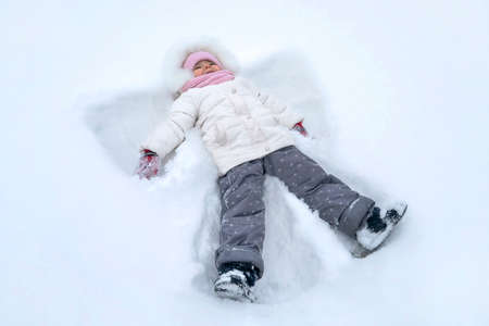 Cute girl child makes snow angel at winter park