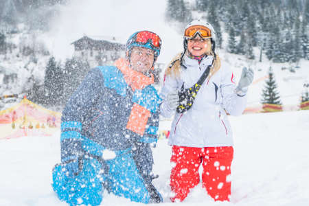 Happy couple people have fun and enjoy the fresh snow in winter mountains Carpathians.