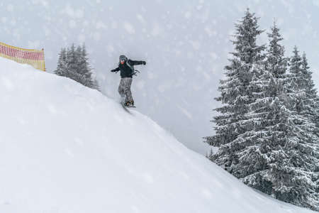 Snowboarder rides from powder snow hill. Mountain freeride snowboarding. Winter Carpathians