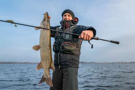 Happy fisherman with big pike fish. Boat fishing