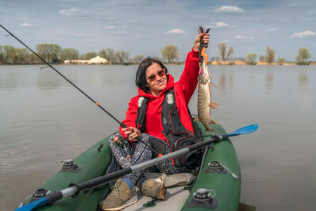 Kayak fishing. Fisher girl holding pike fish trophy on inflatable boat with fishing tackle at lake.