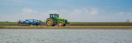 Farmer in tractor preparing land by seedbed cultivator at field near lake