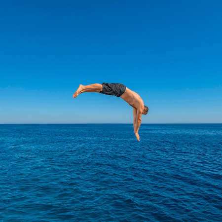 Fly after jump. Man jumping in blue sea water for dive. Summer fun lifestyle