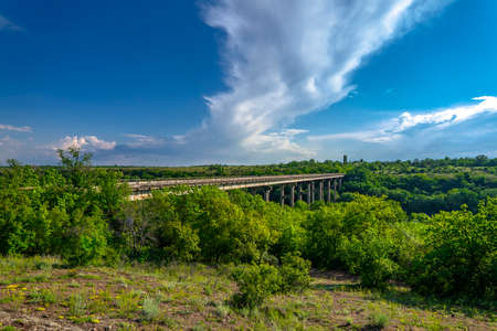 Ancient old bridge over Southern Bug. Yuzhny Buh river flow through green trees. Nature landscape